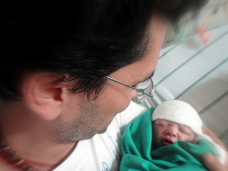 Elisson contemplando o filho recém-nascido, em parto acompanhado por Dr. Renato Janone.